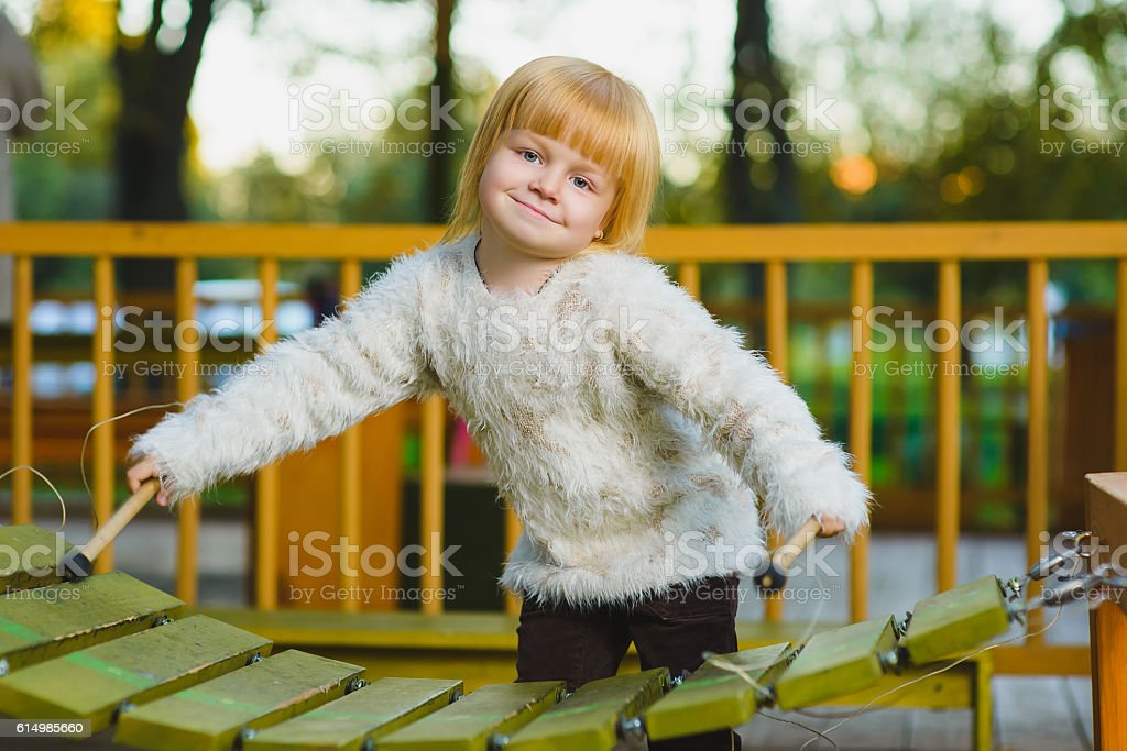Close up portrait of cute girl playing xylophone outdoor stock photo