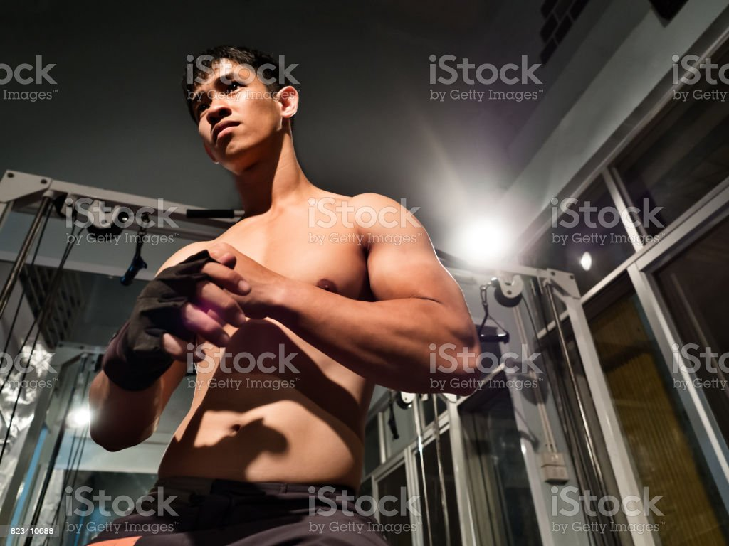 Close up portrait of fitness man and bodybuilder wearing a glove prepare to workout at gym, show upper body, biceps, triceps muscles, arms and torso, Asian look stock photo