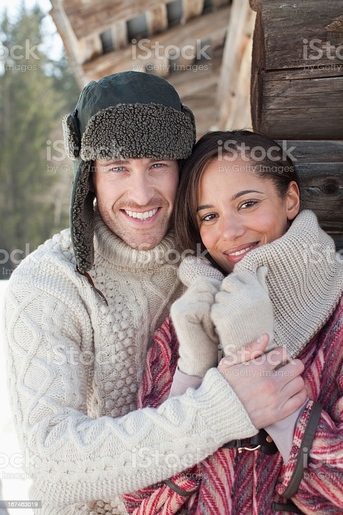 Close up portrait of smiling couple hugging in snow royalty-free stock photo
