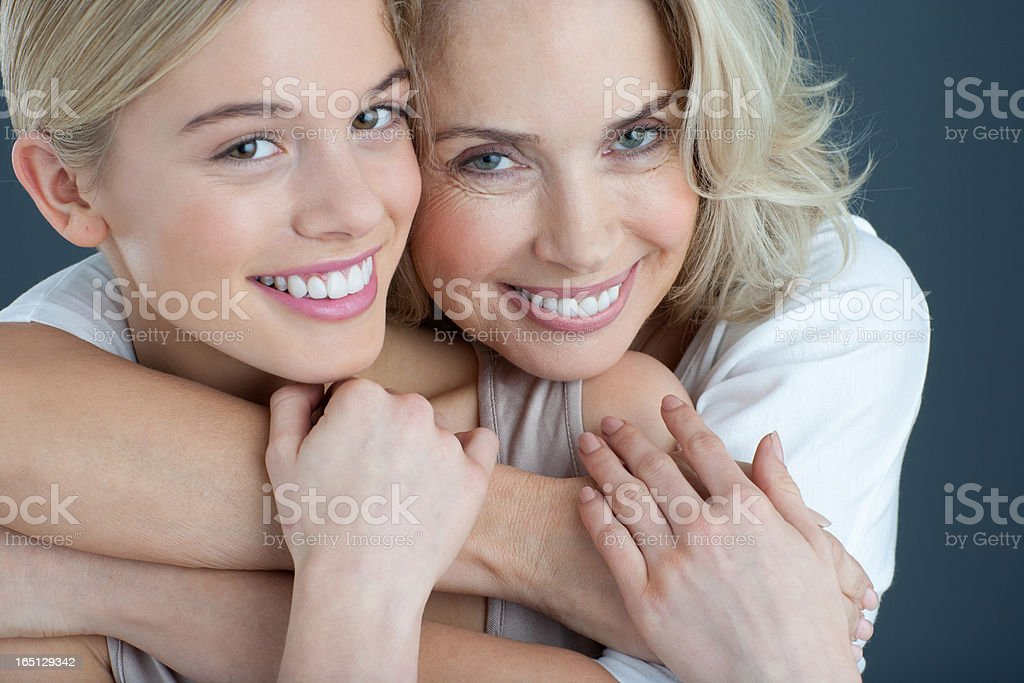 Close up portrait of smiling mother and daughter hugging stock photo