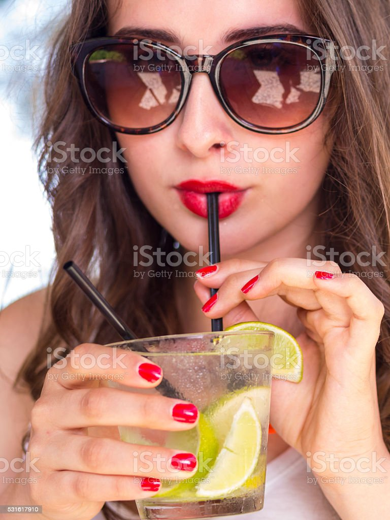 Close up portrait of woman drinking sweet Cocktail stock photo