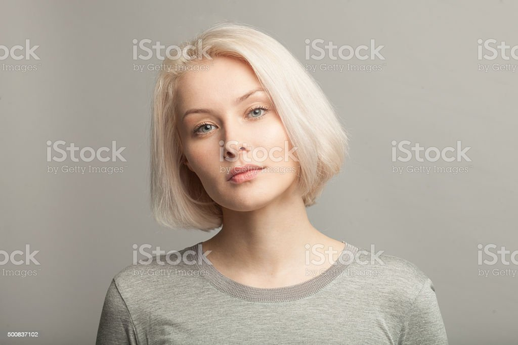 close up portrait of young beautiful blonde woman on gray stock photo
