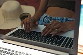 Close up reflection of woman hands typing on laptop