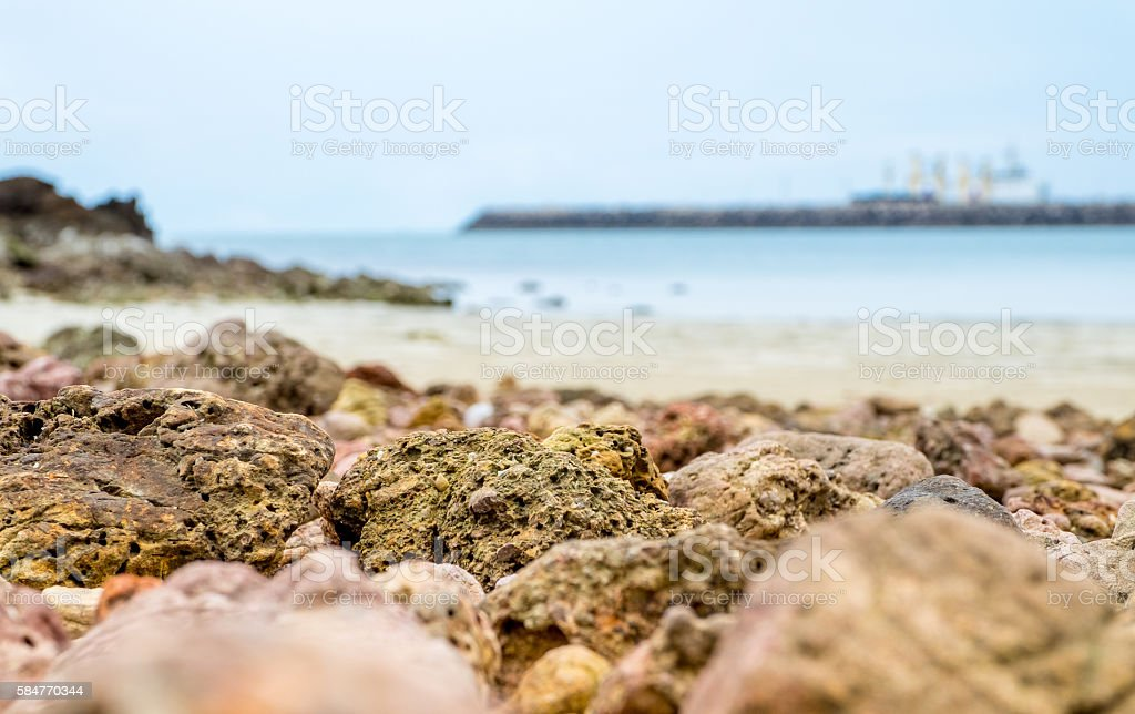 close up sea rock at beach with blur sea line stock photo
