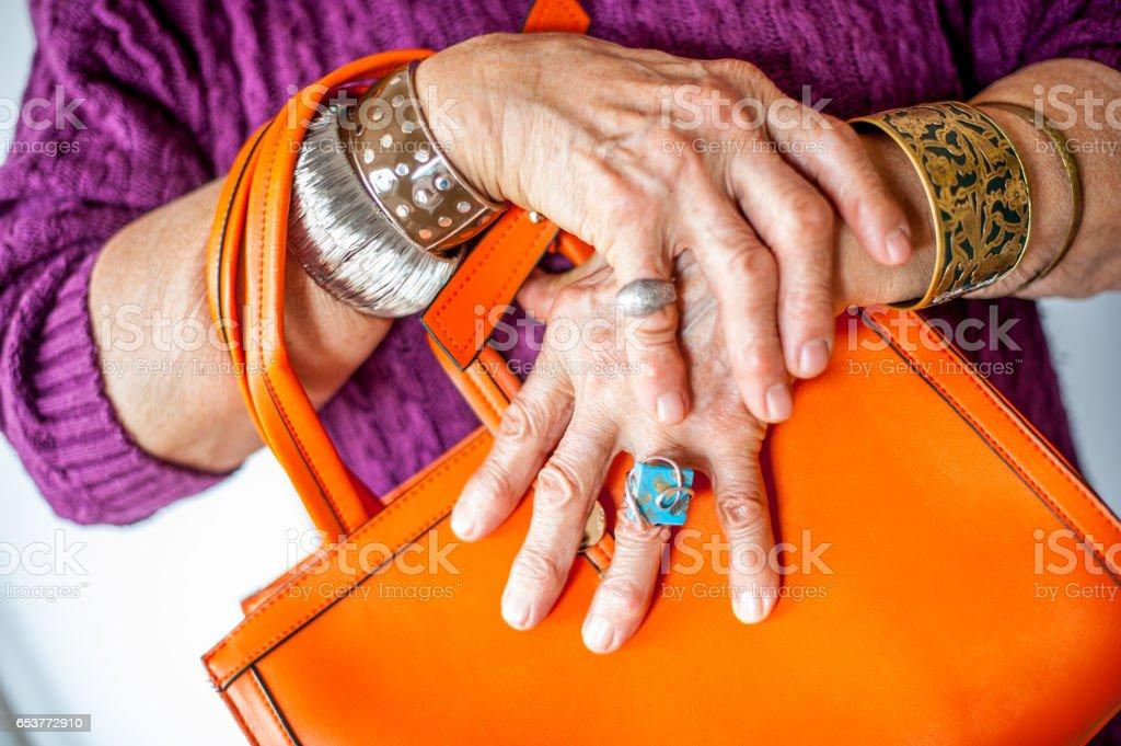 Close Up Senior Woman Wrinkled Hand Holding Handbag stock photo