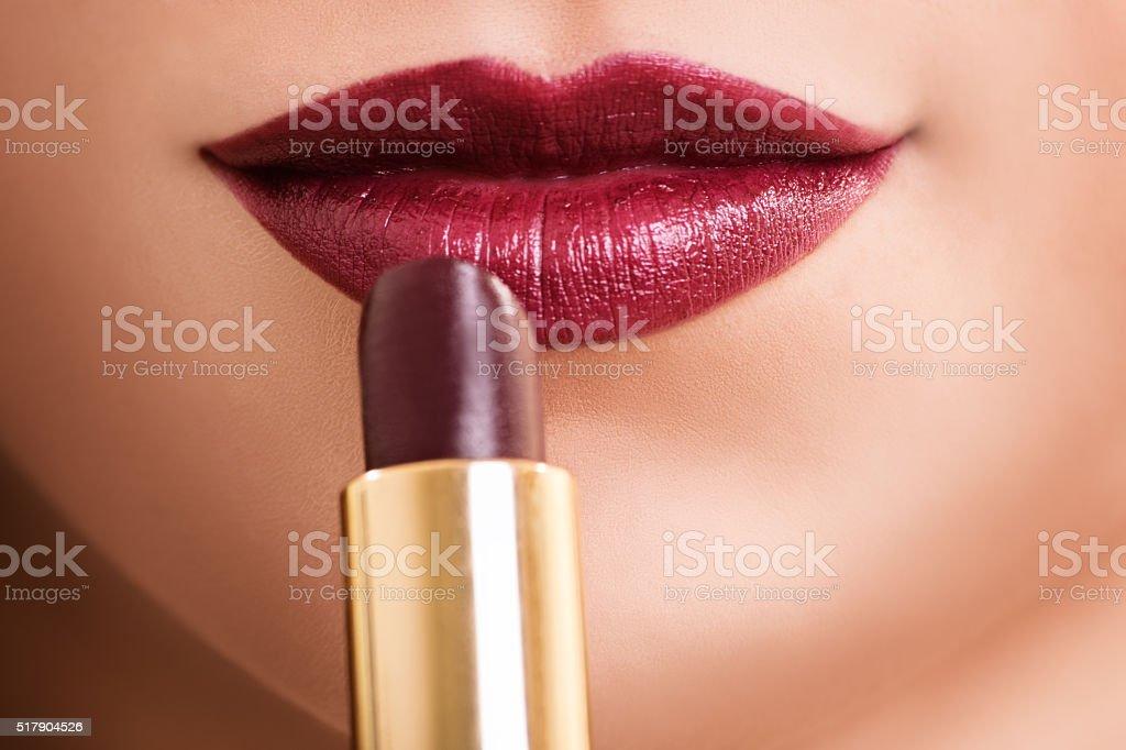 Close up shot of a female mouth putting lipstick stock photo