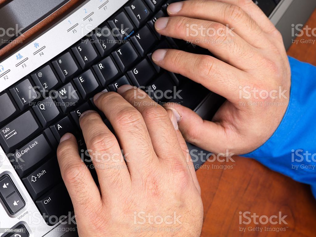 close up shot of a person typing on black keyboard stock photo