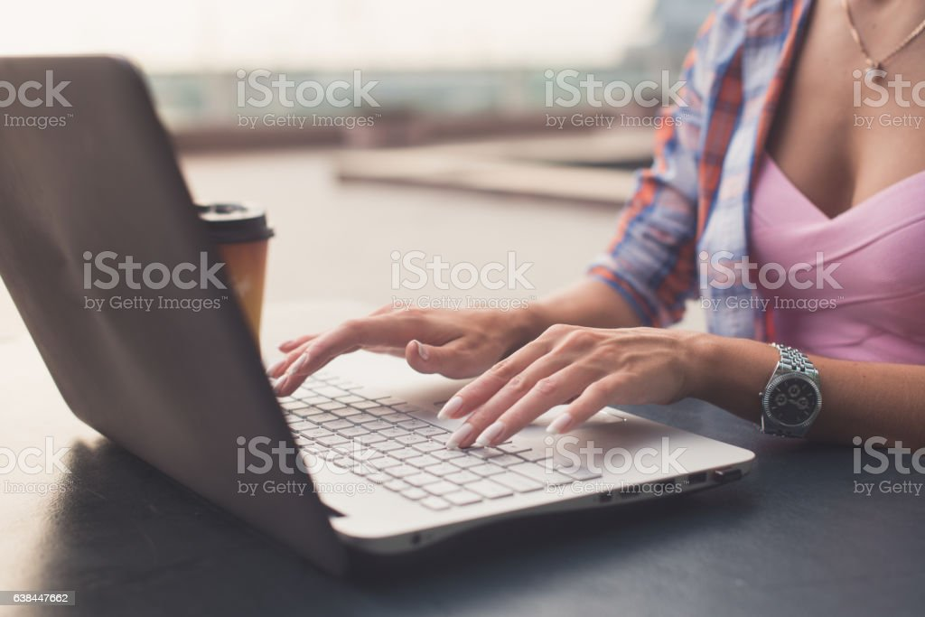 Close up shot of female hands typing on a laptop stock photo