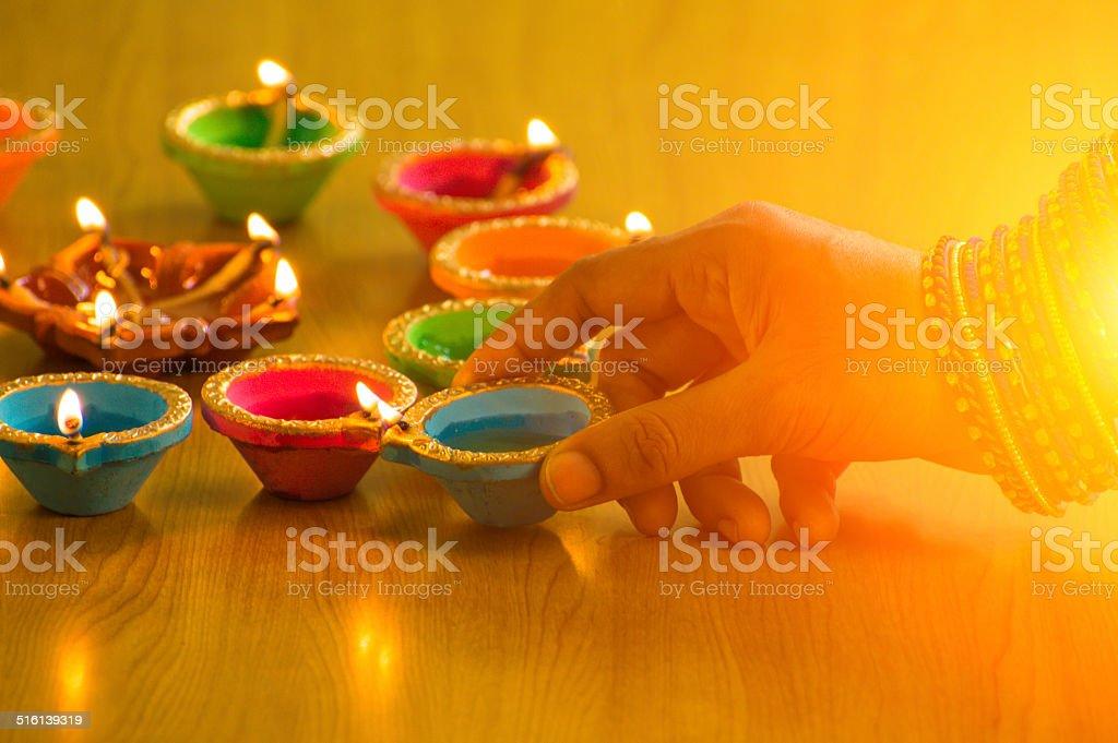close up shot of hand lighting up Diwali lamp stock photo