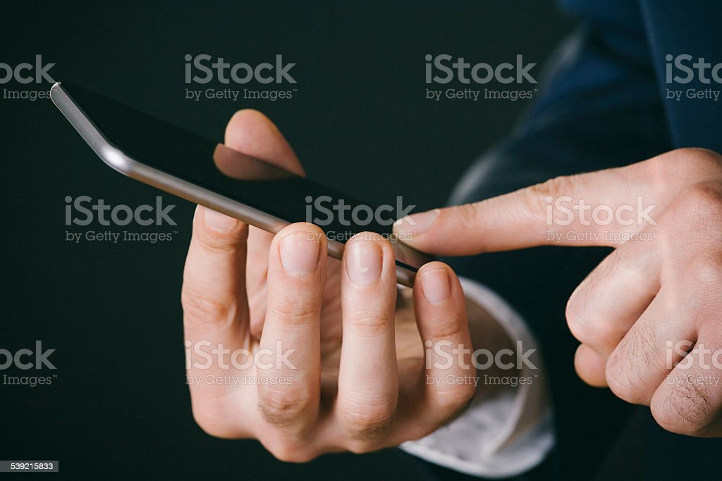 Close up shot of male hands using cell phone stock photo