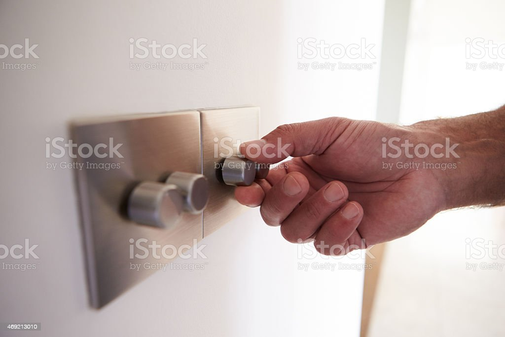 Close Up Shot Of Man Turning Down Electrical Dimmer Switch stock photo