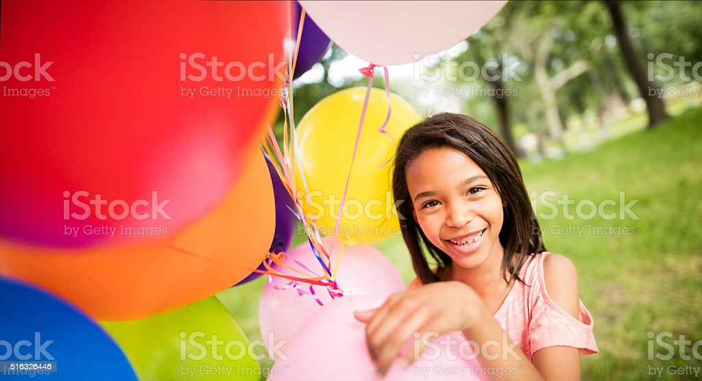 Close up shot of young girl holding bunch of balloons. stock photo