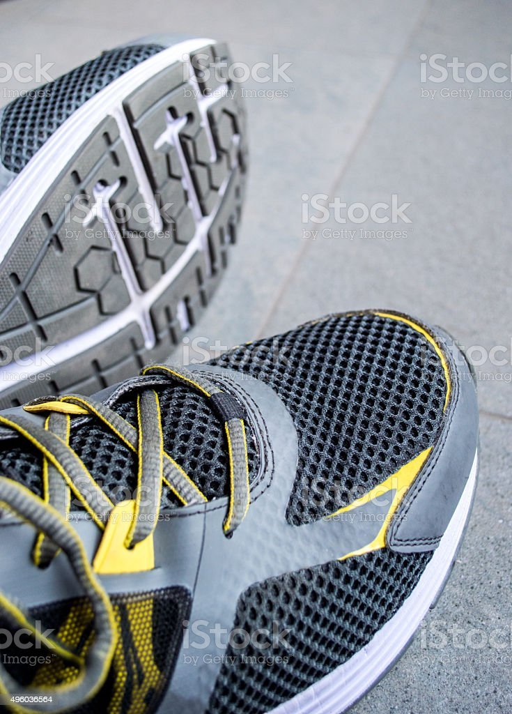 Close Up Side View of Trainer/Running Shoes on Pavement royalty-free stock photo