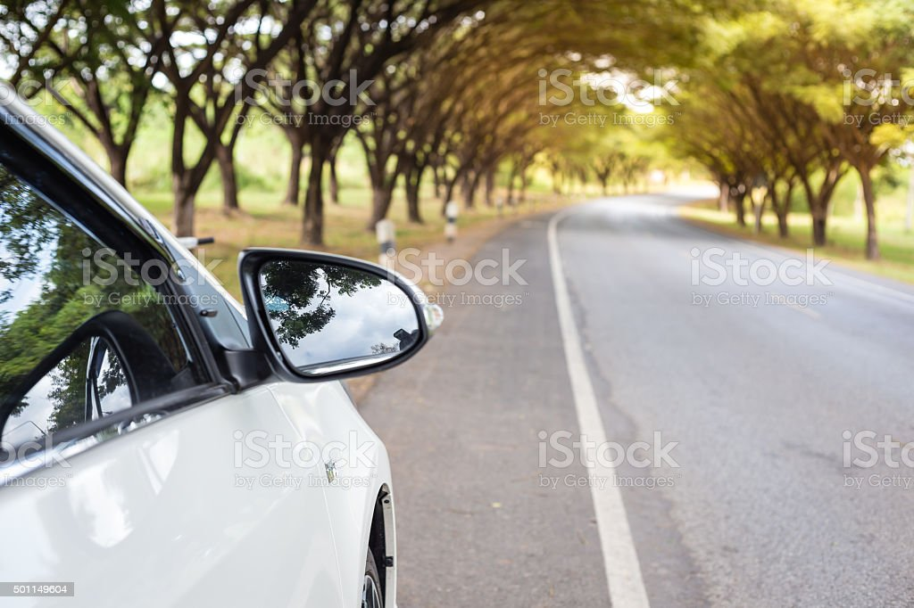 Close up Sideview mirror white cars beside the road. stock photo