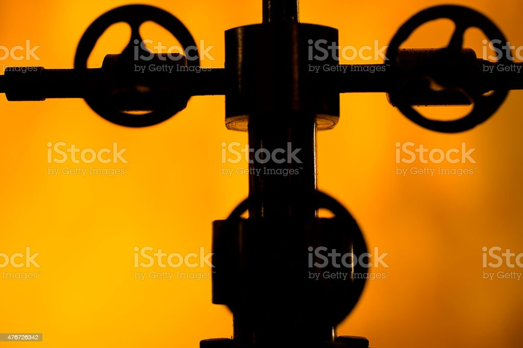 Close up silhouette of oil field 'Christmas Tree' equipment. stock photo