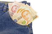 Close up Singapore dollars in a jeans pocket isolated