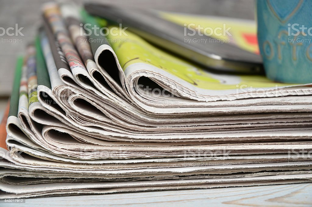 Close up  stacked newspapers with smartphone on wooden table background stock photo