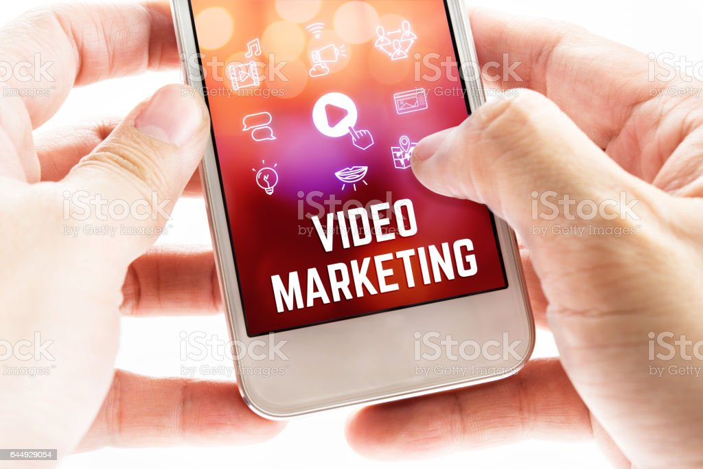 Close up Two hand holding mobile phone with Video marketing word and icons, Online Digital Marketing concept stock photo