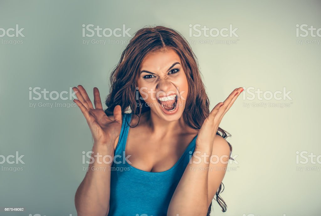 Close up very angry woman screaming in horror, grimace portrait. Stressed frustrated young lady having nervous breakdown isolated green background. Negative human emotion. long working hours concept stock photo