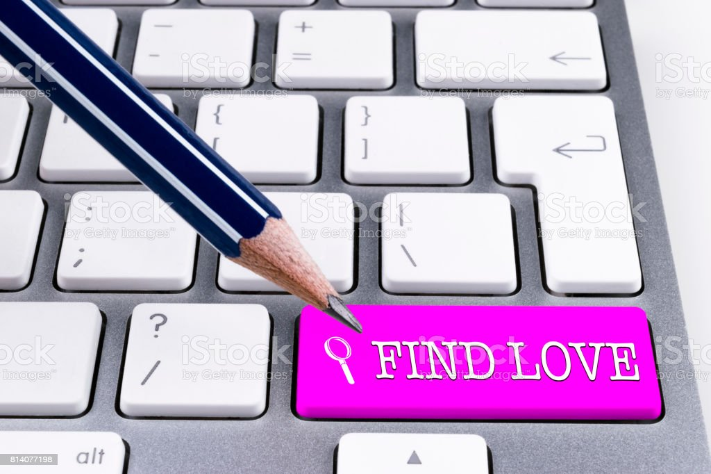 Close up view of a Computer notebook keyboard with office pencil and one pink button FIND LOVE, technology background, empty space for text stock photo
