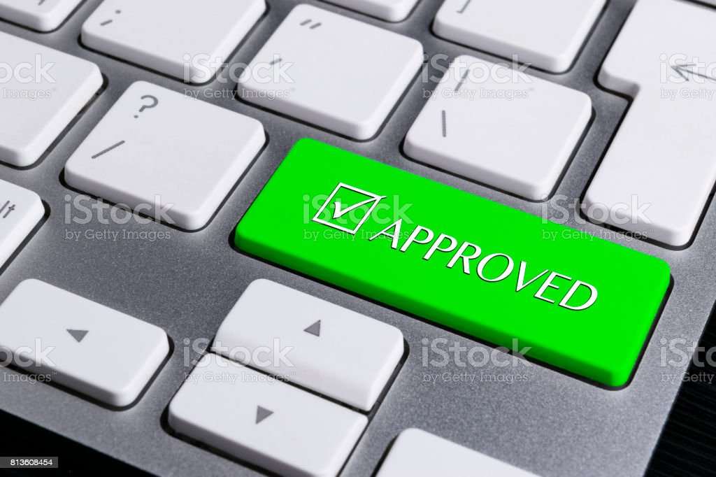 Close up view of a Computer notebook keyboard with one green button with word APPROVED, technology background, empty space for text stock photo