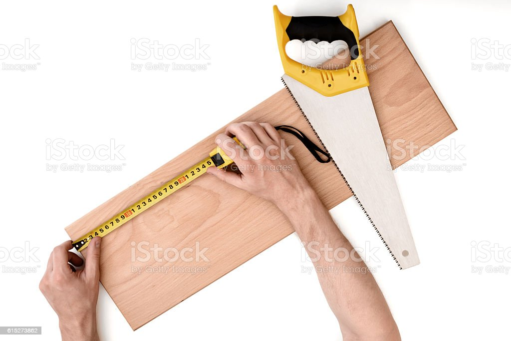 Close up view of a man's hands measuring wooden stock photo