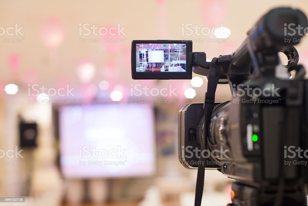 Close up view of a video camera focusing on a subject stock photo