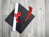 Close up view of black graduation cap on wooden background