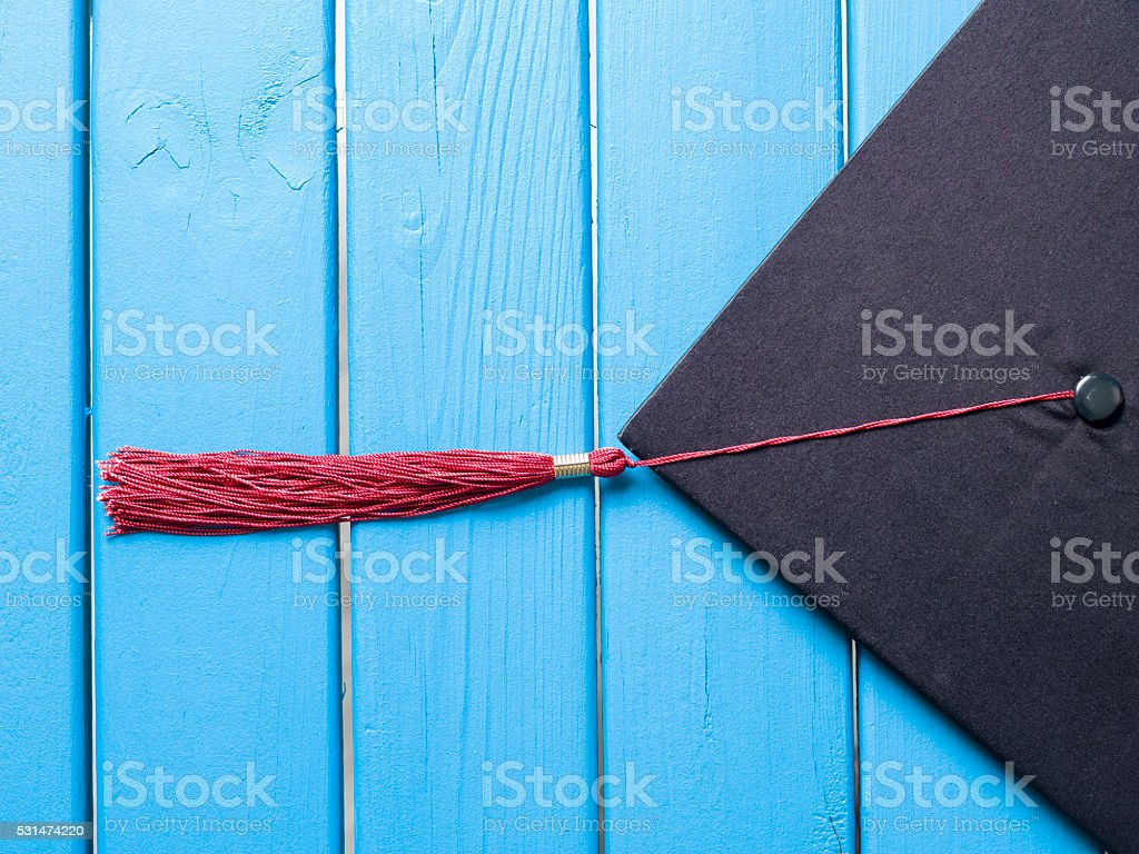 Close up view of black graduation cap on wooden background stock photo