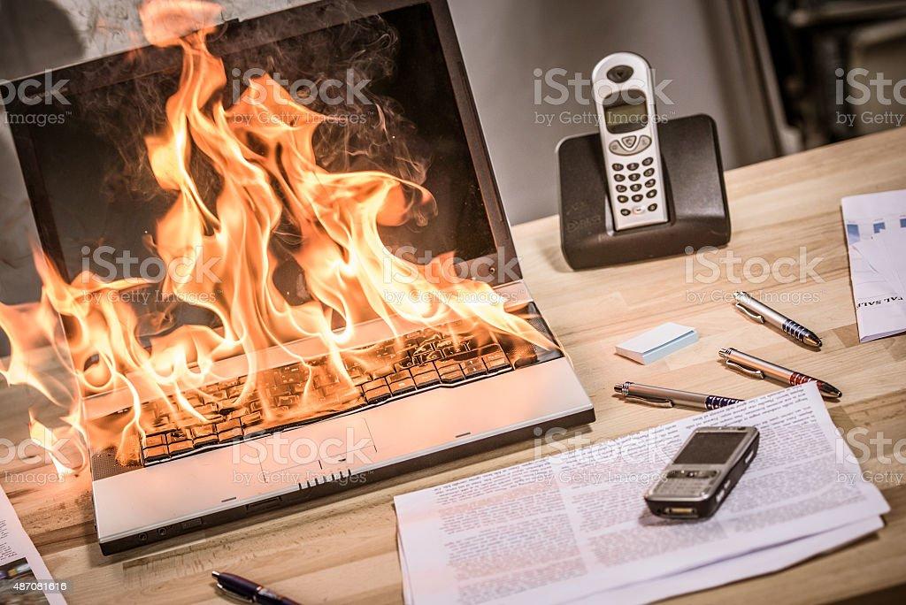 Burning laptop on desk in office.