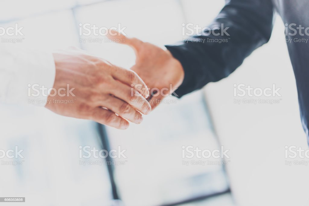 Close up view of business partnership handshake concept.Photo two businessman handshaking process.Successful deal after great meeting.Horizontal, blurred background. stock photo