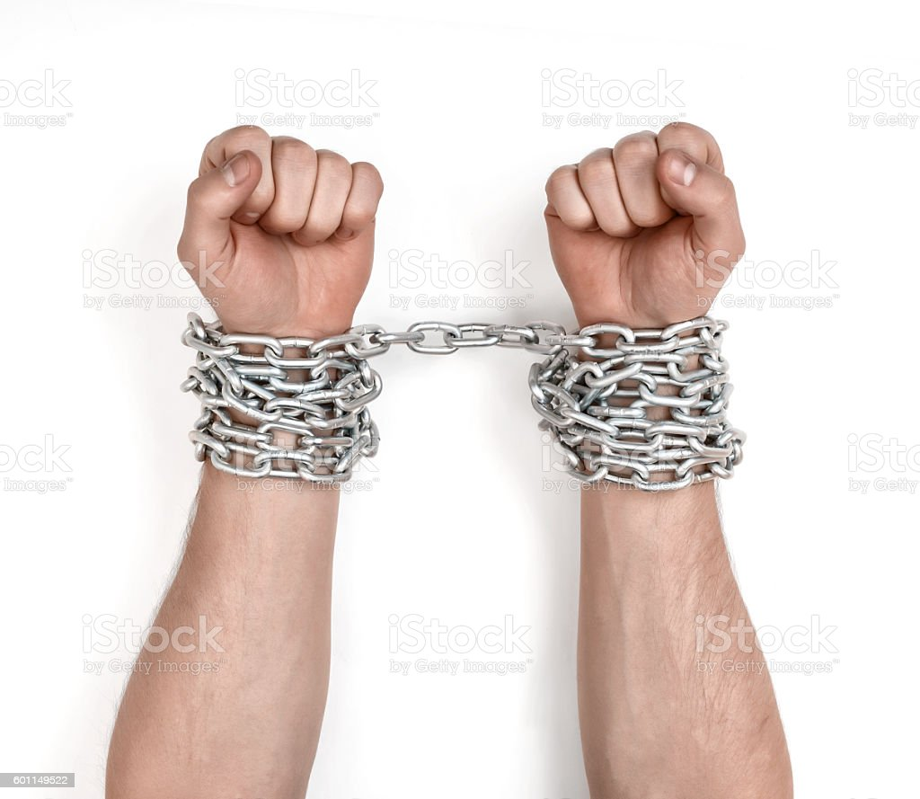 Close up view of chained man's hands stock photo