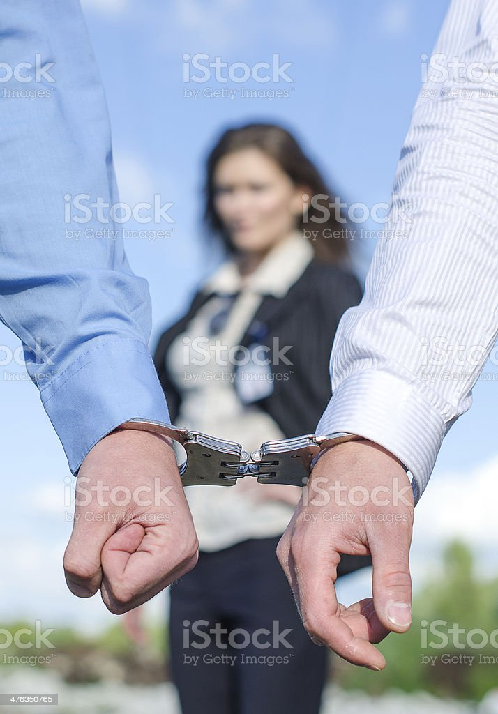 Close up view of hands in handcuffs royalty-free stock photo