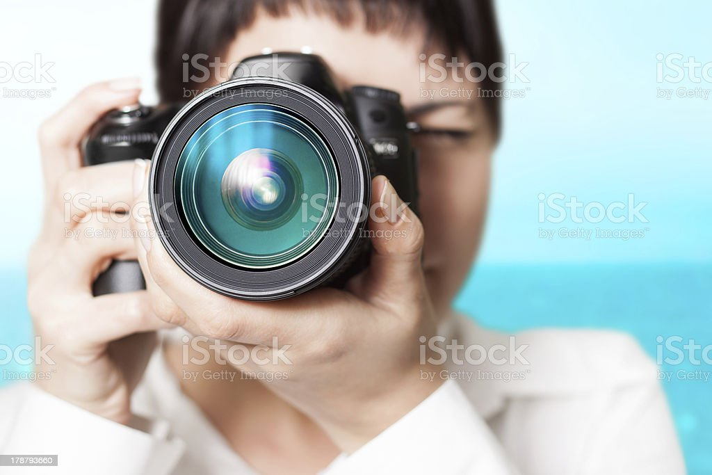 Close up view of lens as woman photographer hold camera royalty-free stock photo