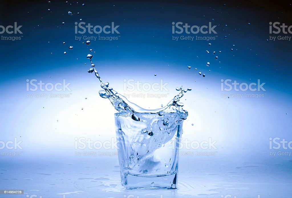 Close up view of the splash in water on blue stock photo