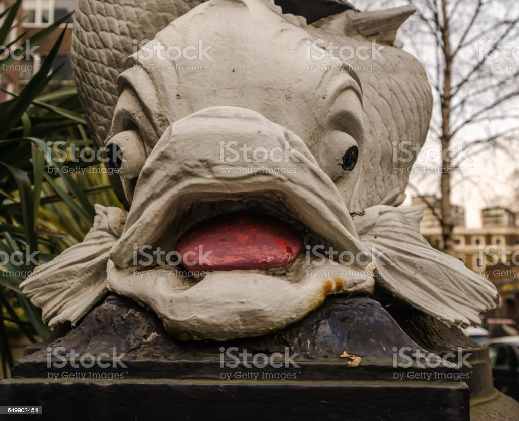 close up view on the characteristic decoration around a street lamp in London, large white ornament in the shape of a fish, london street lamp stock photo