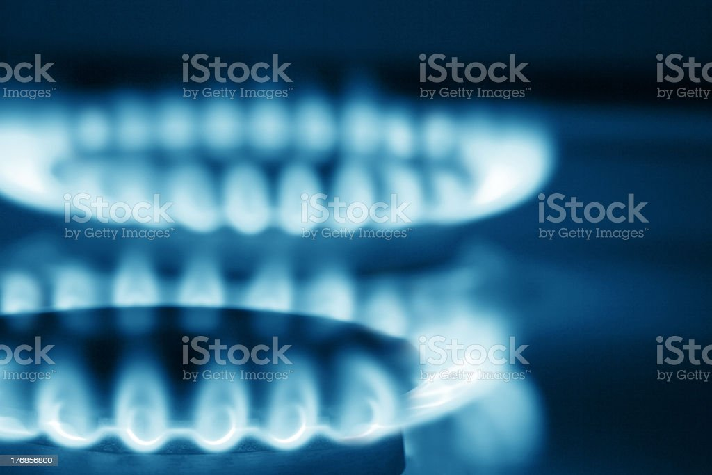 Close up view on two cooker's burners (blue toned) royalty-free stock photo