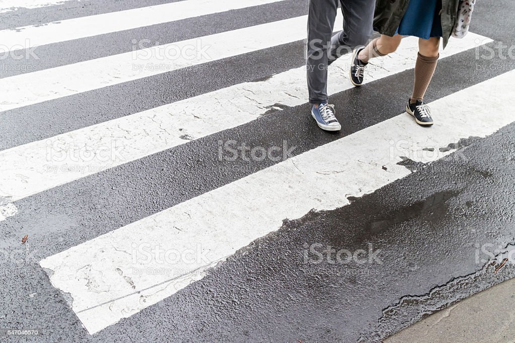 Close up wet crosswalk and walking step on city street. stock photo
