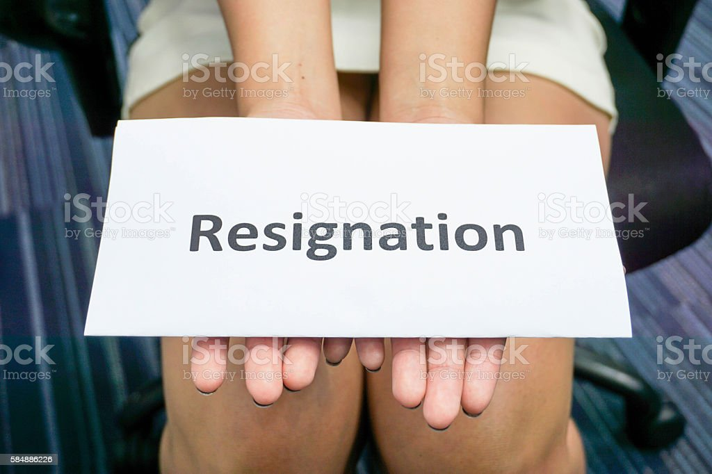 close up woman hands hold a piece of paper of resignation stock photo