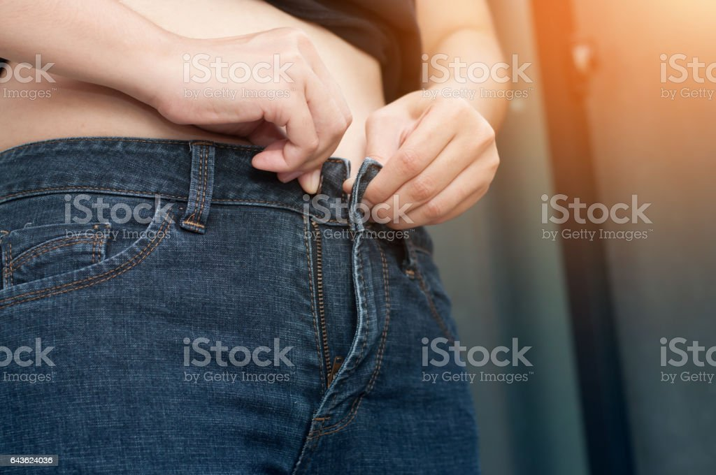 Close up woman hands with belly fat. stock photo
