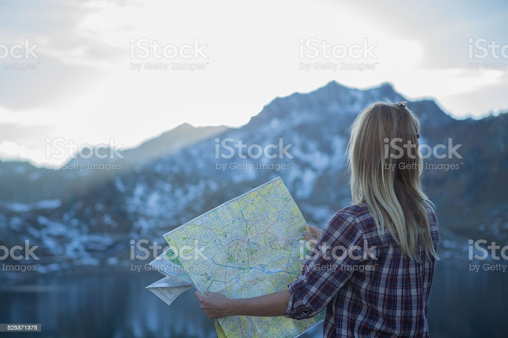 Close up woman tourist hiking in mountain reading map-directions stock photo