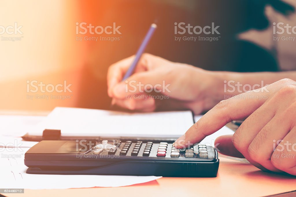 Close up young woman with calculator counting making notes stock photo