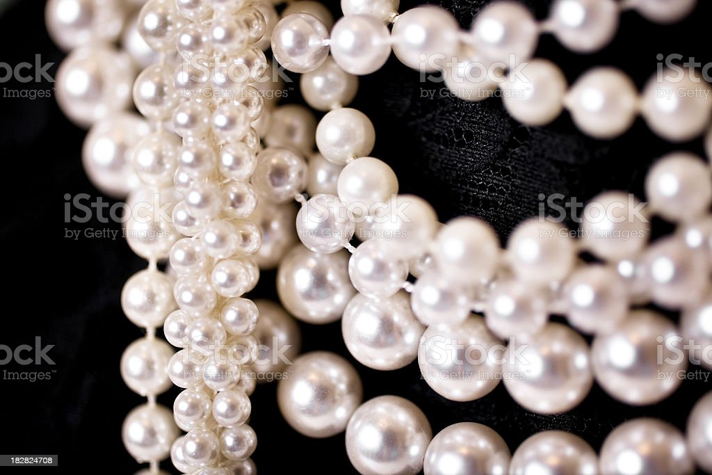 Close upf various strands of pearls on black lace royalty-free stock photo
