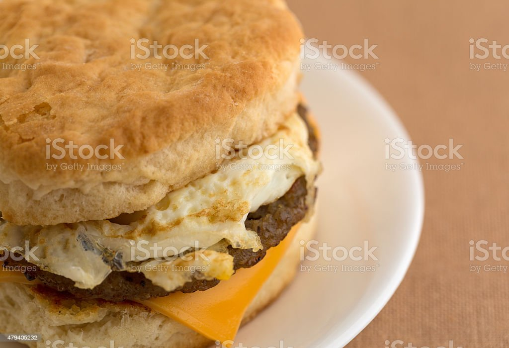 Close view of a breakfast sausage egg and cheese biscuit stock photo