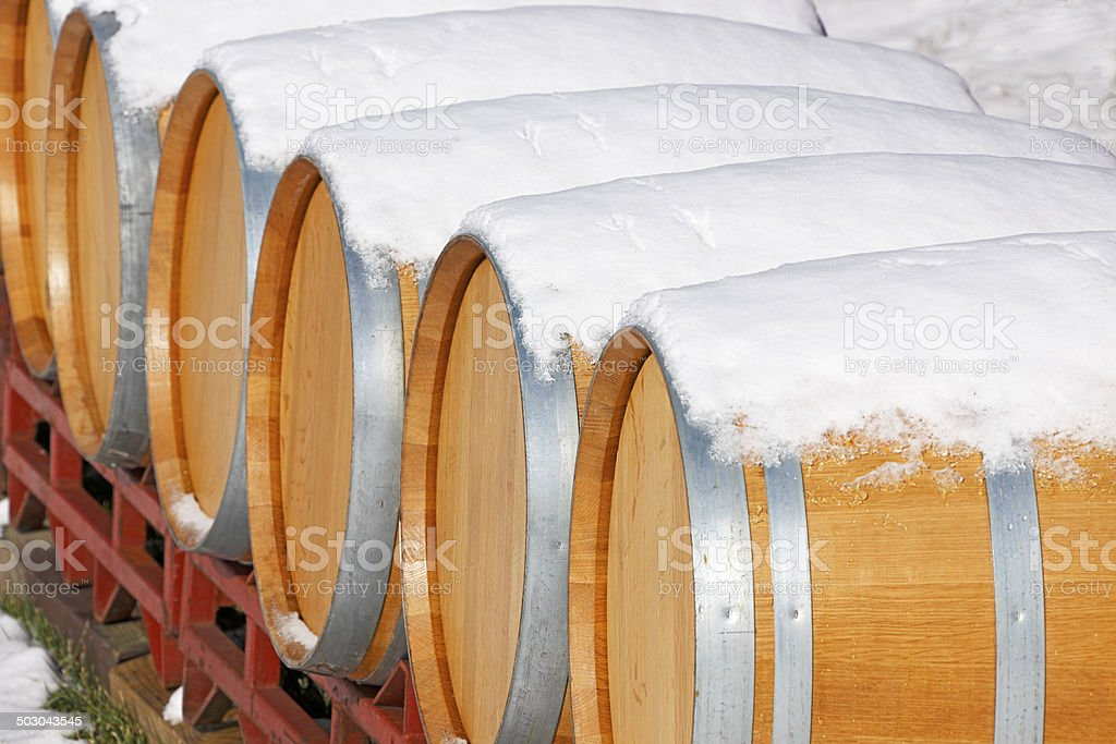 Close view of snow-covered oak wine barrels stock photo
