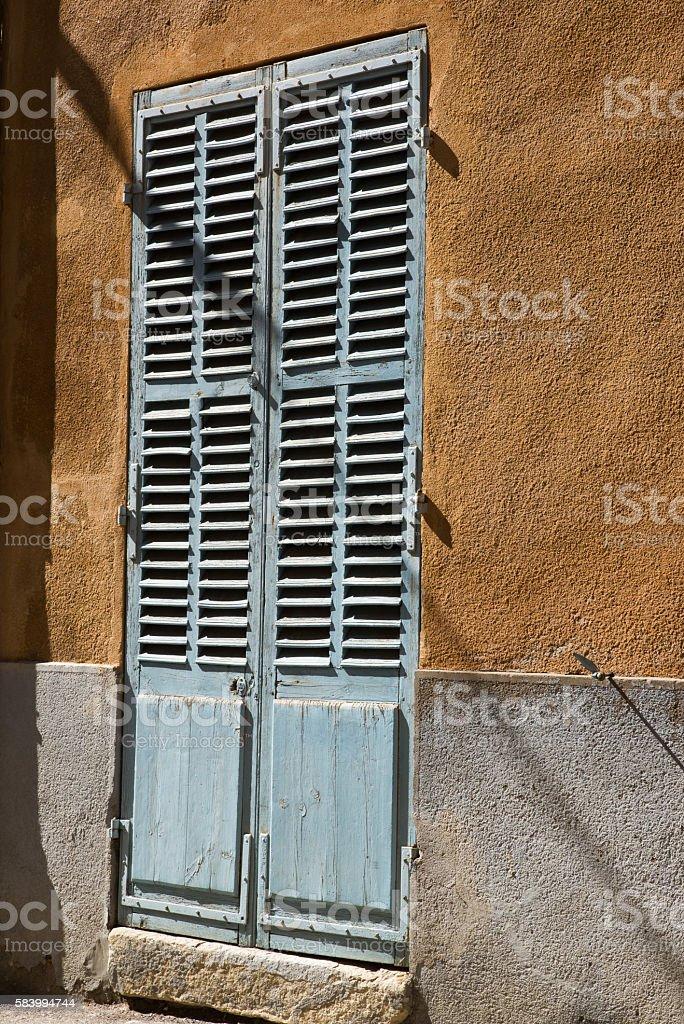 Closed blue wooden door shutters on a ochre wall stock photo