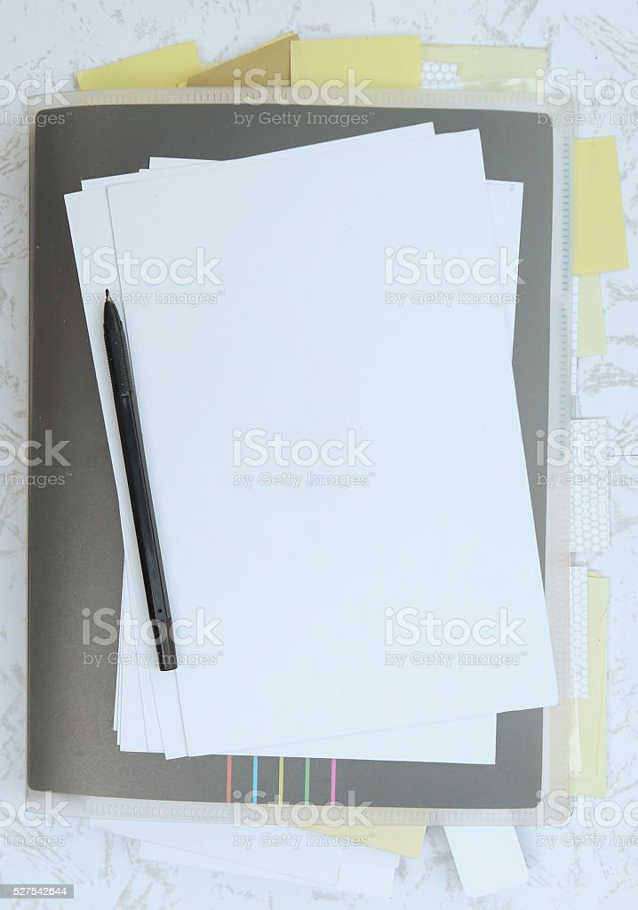 Closed book with sticky notes, papers and pen stock photo