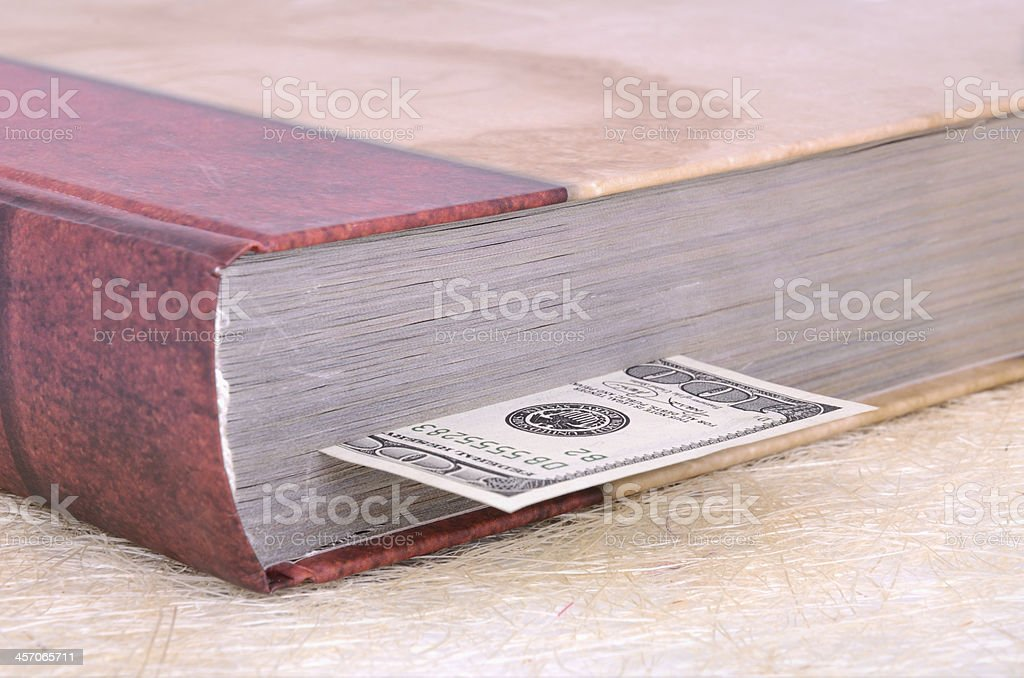 closed brown book with a bookmark 100 USD royalty-free stock photo