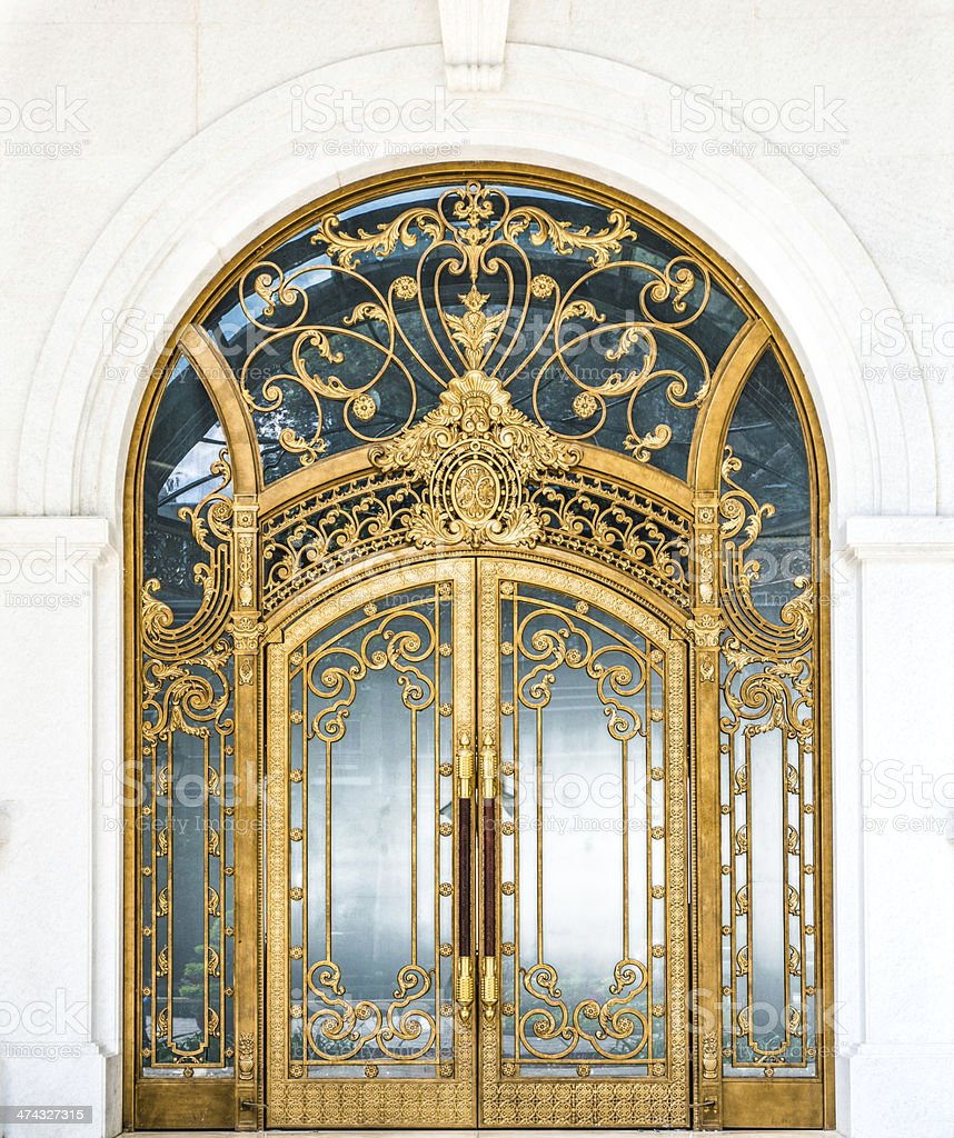 Closed door of building with gold ornate pattern. stock photo