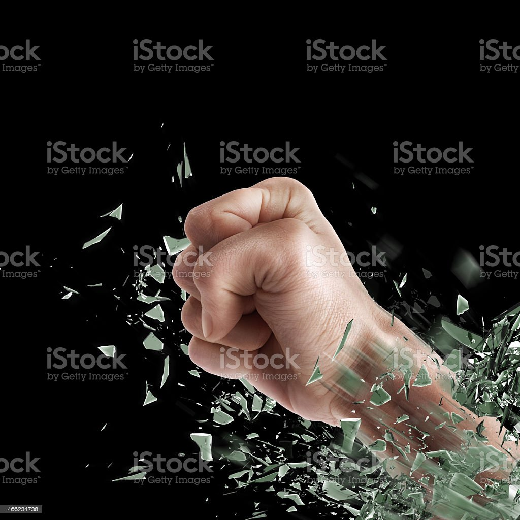 Closed fist shattering glass over a black background stock photo